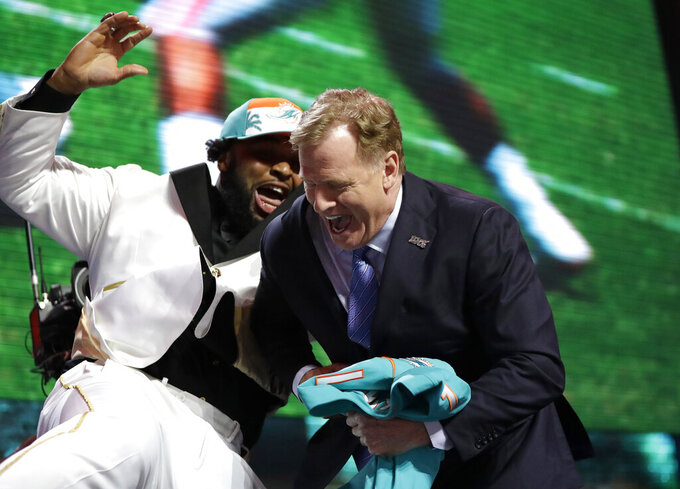 Clemson defensive tackle Christian Wilkins moves into NFL Commissioner Roger Goodell after the Miami Dolphins selected Wilkins in the first round at the NFL football draft, Thursday, April 25, 2019, in Nashville, Tenn. (AP Photo/Mark Humphrey)