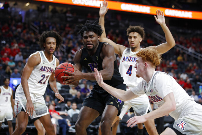 Washington's Isaiah Stewart (33) grabs a rebound over Arizona's Nico Mannion, right, during the first half of an NCAA college basketball game in the first round of the Pac-12 men's tournament Wednesday, March 11, 2020, in Las Vegas. (AP Photo/John Locher)