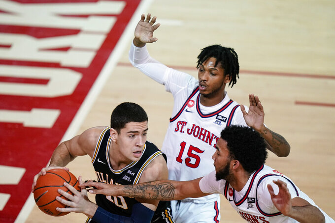 Villanova's Cole Swider (10) protects the ball from St. John's Julian Champagnie and Vince Cole (15) during the first half of an NCAA college basketball game Wednesday, Feb. 3, 2021, in New York. (AP Photo/Frank Franklin II)