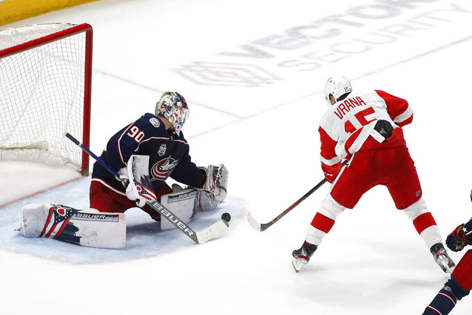 Columbus Blue Jackets' Elvis Merzlikins, left, makes a save against Detroit Red Wings' Jakub Vrana during overtime in an NHL hockey game Tuesday, April 27, 2021, in Columbus, Ohio. The Blue Jackets won 1-0 in a shootout. (AP Photo/Jay LaPrete)