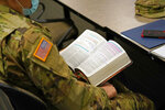 Minnesota National Guard chaplain Charles Kim, a pastor at Korean Presbyterian Church, holds his Bible during a time of devotion for fellow chaplains Oct. 19, 2020 in St. Paul, Minn.  The role of faith leaders who serve as National Guard chaplains has grown more crucial, and more challenging, as thousands of soldiers and airmen, most of them in their 20s, have been increasingly deployed not only in long-lasting overseas wars but in civil unrest across a deeply polarized United States. (AP Photo/Jim Mone)