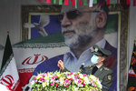 In this photo released by the official website of the Iranian Defense Ministry, Defense Minister Gen. Amir Hatami speaks during a funeral ceremony for Mohsen Fakhrizadeh, a scientist who was killed on Friday, shown in the banner at background, in Tehran, Iran, Monday, Nov. 30, 2020. Iran held the funeral Monday for the slain scientist who founded its military nuclear program two decades ago, with the Islamic Republic's defense minister vowing to continue the man's work