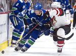 Vancouver Canucks left wing Antoine Roussel (26) fights for control of the puck with Arizona Coyotes defenseman Ilya Lyubushkin (46) during the second period of an NHL hockey game Thursday, Jan. 16, 2020, in Vancouver, British Columbia. (Jonathan Hayward/The Canadian Press via AP)