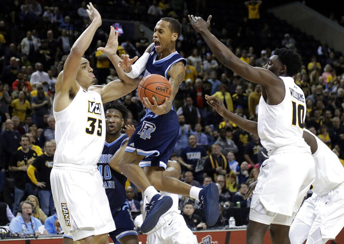 Rhode Island's Fatts Russell, center, drives against VCU's Vince Williams, right, and Marcus Santos-Silva, left, during the second half of an NCAA college basketball game in the Atlantic 10 men's tournament Friday, March 15, 2019, in New York. Rhode Island won 75-70. (AP Photo/Frank Franklin II)