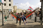 Anti-government protesters rest in a hammock hanging from a traffic sign post during a protest in Beirut, Lebanon, Saturday, Oct. 19, 2019. The blaze of protests was unleashed a day earlier when the government announced a slate of new proposed taxes, including a $6 monthly fee for using Whatsapp voice calls. The measures set a spark to long-smoldering anger against top leaders from the president and prime minister to the numerous factional figures many blame for decades of corruption and mismanagement. (AP Photo/Hassan Ammar)