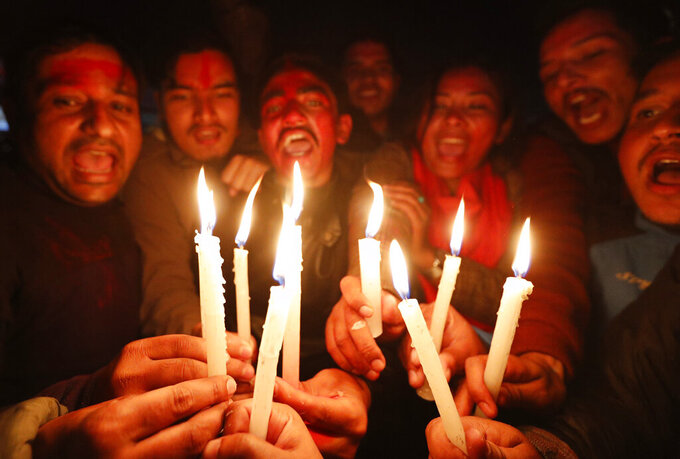 Nepalese supporters of the splinter group in the governing Nepal Communist Party celebrate the Supreme Court order in Kathmandu, Nepal, Tuesday, Feb. 23, 2021. Nepal's Supreme Court on Tuesday ordered the reinstatement of Parliament after it was dissolved by the prime minister, in a ruling likely to thrust the Himalayan nation into a political crisis. (AP Photo/Niranjan Shrestha)