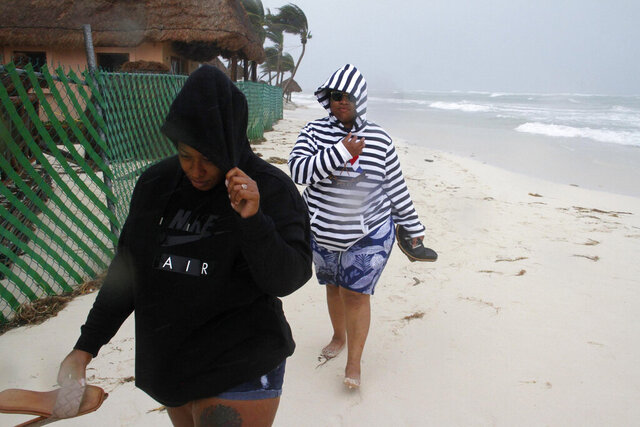 Tourists walk on the beach as the tail end of Hurricane Zeta makes landfall in Playa del Carmen, Mexico, early Tuesday, Oct. 27, 2020. Zeta is leaving Mexico's Yucatan Peninsula on a path that could hit New Orleans Wednesday night. (AP Photo/Tomas Stargardter)