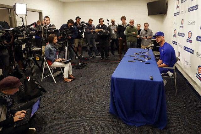 Chicago Cubs third baseman Kris Bryant, right, speaks to reporters during spring training baseball Saturday, Feb. 15, 2020, in Mesa, Ariz. (AP Photo/Gregory Bull)