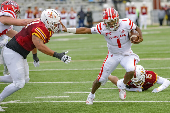 Louisiana-Lafayette quarterback Levi Lewis (1) scores a touchdown against Louisiana-Monroe defensive lineman Seth Mason (94) during the first half of an NCAA college football game in Monroe, La., Saturday, Nov. 28, 2020. (AP Photo/Matthew Hinton)