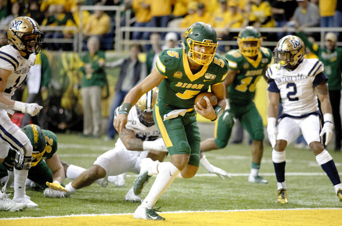 FILE - In this Dec. 21, 2019, file photo, North Dakota State quarterback Trey Lance (5) scores a rushing touchdown during the first half of an FCS playoff NCAA college football game against Montana State in Fargo, N.D. All but a few teams in the Football Championship Subdivision shut down in the fall because of the COVID-19 pandemic and will play a spring season culminating with the NCAA playoffs in April and May. (AP Photo/Bruce Crummy, File)