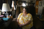 """Doris Kelly, 57, sits in her home on Monday, June 29, 2020 in Ruffs Dale, Pa. Kelly was one of the first patients in a UPMC trial for COVID-19. """"It felt like someone was sitting on my chest and I couldn't get any air,"""" Kelley said of the disease. (AP Photo/Justin Merriman)"""