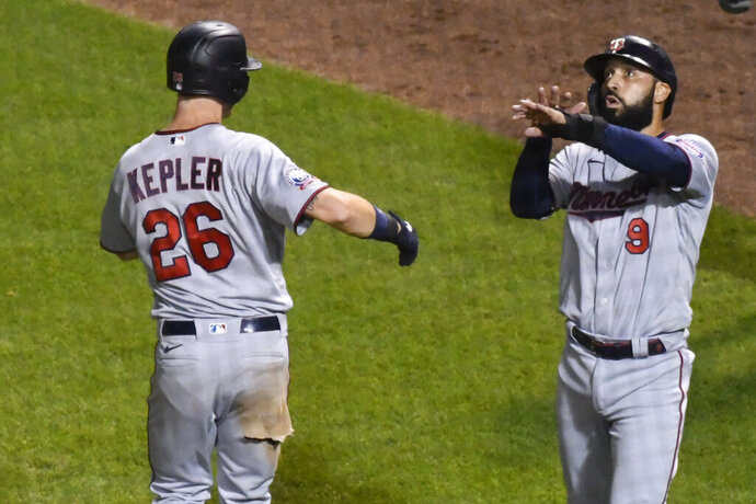 Minnesota Twins' Max Kepler (26) celebrates with Minnesota Twins' Marwin Gonzalez (9) after they score on Kepler's two-run home run during the seventh inning of a baseball game against the Chicago Cubs Sunday, Sept. 20, 2020, in Chicago. (AP Photo/Matt Marton)