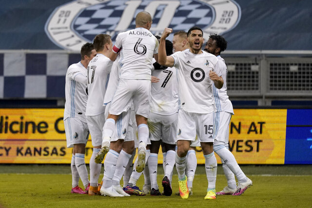 Minnesota United players celebrate after a goal by Bakaye Dibassy during the first half of an MLS soccer match against Sporting Kansas City on Thursday, Dec. 3, 2020, Kansas City, Kan. (AP Photo/Charlie Riedel)