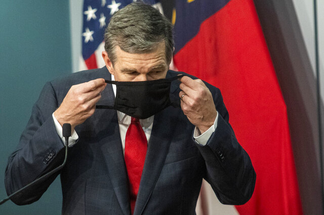 Gov. Roy Cooper removes his mask before answering a reporter's question during a briefing on North Carolina's coronavirus pandemic response at the North Carolina Emergency Operations Center, Wednesday, Sept. 30, 2020, in Raleigh, N.C. (Travis Long/The News & Observer via AP)