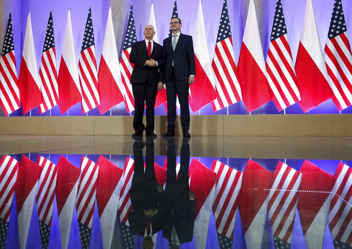 United States Vice President Mike Pence, left, and Poland's Prime Minister Mateusz Morawiecki, right, shake hands prior to a meeting at the Chacellery in Warsaw, Poland, Thursday, Feb. 14, 2019. The Polish capital is host for a two-day international conference on the Middle East, co-organized by Poland and the United States. (AP Photo/Michael Sohn)