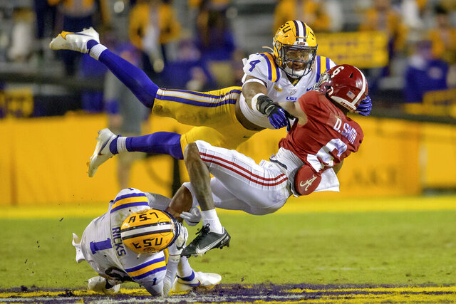 Alabama wide receiver DeVonta Smith (6) tries to avoid a flying tackle by LSU safety Todd Harris Jr. (4) and cornerback Eli Ricks (1) in the second half of an NCAA college football game in Baton Rouge, La., Saturday, Dec. 5, 2020. (AP Photo/Matthew Hinton)