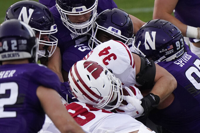 Wisconsin fullback Mason Stokke (34) is tackled by a host of Northwestern defenders during the first half of an NCAA college football game in Evanston, Ill., Saturday, Nov. 21, 2020. Northwestern won 17-7. (AP Photo/Nam Y. Huh)