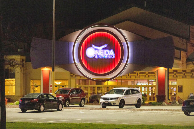 The Oneida Casino lights glow in the parking lot in the early morning hours of Sunday, May 2nd, 2021, near Green Bay, Wisconsin. Authorities in Wisconsin say a gunman killed two people at a Green Bay casino restaurant and seriously wounded a third before he was shot and killed by police Saturday. (AP Photo/Mike Roemer)