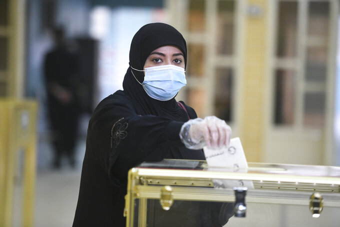 A woman casts her vote for parliamentary elections in the town of Hawally, Kuwait, Saturday, Dec. 5, 2020. (AP Photo/Jaber Abdulkhaleg)