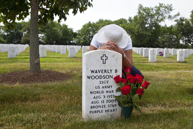 In this undated photo provided by Linda Hervieux,  Joann Woodson kneels at the gravesite of her husband Cpl. Waverly B. Woodson Jr. at Arlington National Cemetery in Arlington, Va. Members of Congress on Tuesday, Sept. 8, 2020 said Woodson Jr., a Black army medic who saved dozens of wounded troops on the beaches of Normandy on D-Day despite being severely wounded himself, deserves the Medal of Honor, as they announced legislation to posthumously award it to him.  (Linda Hervieux via AP, File)