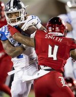Louisville safety TreSean Smith (4) tackles Kentucky wide receiver Lynn Bowden Jr. (1) during the first half of an NCAA college football game in Louisville, Ky., Saturday, Nov. 24, 2018. (AP Photo/Bryan Woolston)