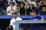 Los Angeles Dodgers manager Dave Roberts, left, and bench coach Bob Geren react after a solo home run by Mookie Betts during the third inning of a baseball game against the Atlanta Braves, Monday, Aug. 30, 2021, in Los Angeles. (AP Photo/Marcio Jose Sanchez)