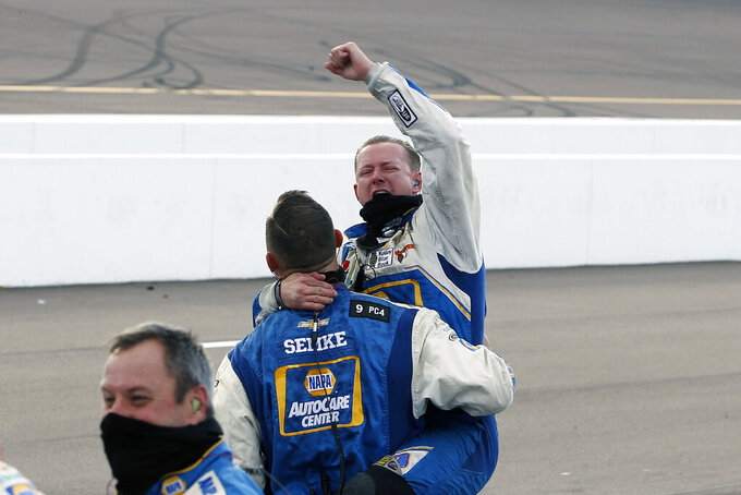 Members of Chase Elliott's pit crew celebrate in their pit stall after winning the season championship and the NASCAR Cup Series auto race at Phoenix Raceway, Sunday, Nov. 8, 2020, in Avondale, Ariz. (AP Photo/Ralph Freso)