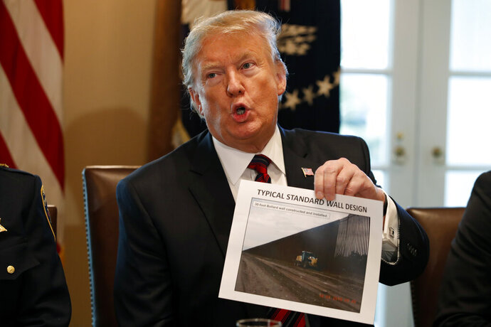 President Donald Trump holds a photo as he leads a roundtable discussion on border security with local leaders, Friday Jan. 11, 2019, in the Cabinet Room of the White House in Washington. (AP Photo/Jacquelyn Martin)