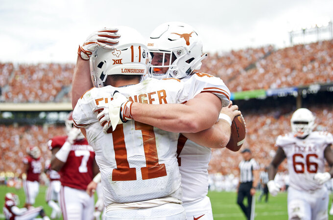 FILE - In this Oct. 6, 2018, file photo, Texas quarterback Sam Ehlinger (11) celebrates with teammate Andrew Beck (47) after scrambling 9-yards for a touchdown against Oklahoma in the first half of an NCAA college football game at the Cotton Bowl in Dallas. No. 5 Oklahoma and No. 9 Texas are playing in a rare Red River rivalry rematch in the Big 12 championship game on Saturday. It is the first time in 115 years that the border state rivals will play twice in the same season.  (AP Photo/Cooper Neill, File)