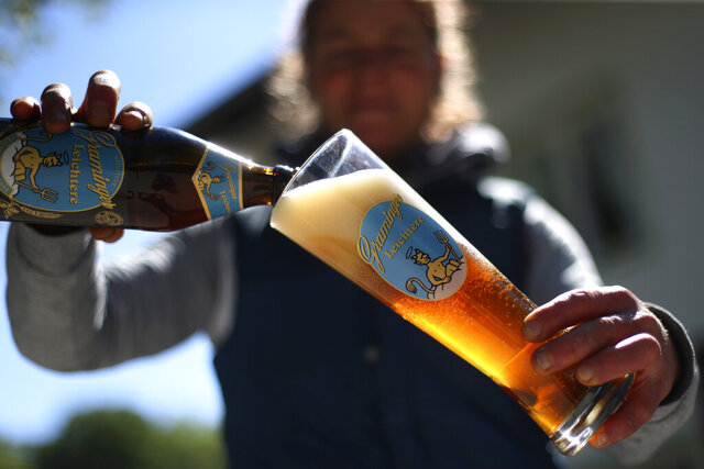 In this photo taken Thursday, May 7, 2020 brewery daughter Iris Detter pours a beer outside her 120 year old family brewery and traditional Bavarian restaurant in Altoetting, Germany. The 'Graminger Weissbraeu' brewery, which has been in the same family for a century, is preparing to welcome guests back to its restaurant for the first time in two months — with new rules and fears for the future. (AP Photo/Matthias Schrader)