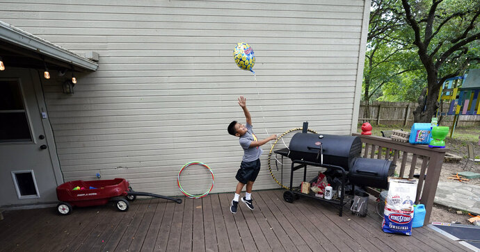 Byron Xol, an immigrant from Guatemala, plays with a balloon before his birthday party Sunday, June 23, 2019, in Buda, Texas. Byron, now staying with the Sewell family, was separated from his father, David Xol, in May 2018, during the Trump's administration wide-scale separation of immigrant families. (AP Photo/David J. Phillip)