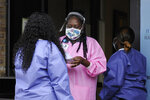 "In this May 27, 2020, photo, health care workers talk outside a Lowndes County coronavirus testing site in Hayneville, Ala. Experts say Lowndes County and nearby poor, mostly black counties in rural Alabama are now facing a ""perfect storm"" as infections tick up: a lack of access to medical care combined with poverty and the attendant health problems that can worsen the outcomes for those who become sick. (AP Photo/Jay Reeves)"
