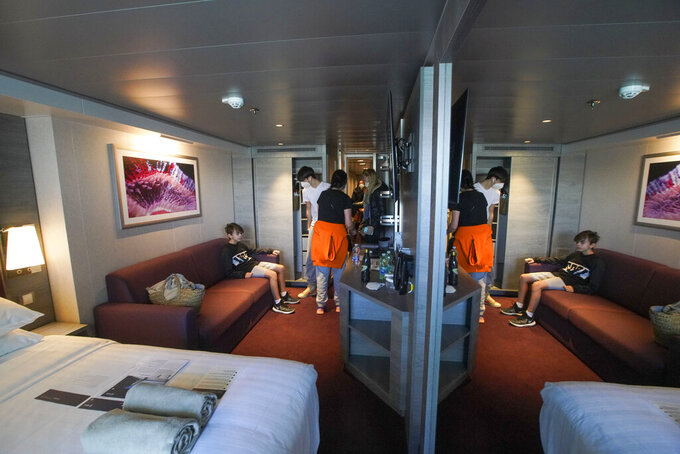 Passengers, from left, Dasteen and Samuel Pacifici, and Stefania Battistoni and Loredana Merlo enter their cabin after boarding the MSC Grandiosa cruise ship in Civitavecchia, near Rome, Wednesday, March 31, 2021. MSC Grandiosa, the world's only cruise ship to be operating at the moment, left from Genoa on March 30 and stopped in Civitavecchia near Rome to pick up more passengers and then sail toward Naples, Cagliari, and Malta to be back in Genoa on April 6. For most of the winter, the MSC Grandiosa has been a lonely flag-bearer of the global cruise industry stalled by the pandemic, plying the Mediterranean Sea with seven-night cruises along Italy's western coast, its major islands and a stop in Malta. (AP Photo/Andrew Medichini)