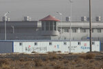 FILE - In this Monday, Dec. 3, 2018, file photo, a guard tower and barbed wire fences are seen around a facility in the Kunshan Industrial Park in Artux in western China's Xinjiang region. China has responded with swift condemnation on Wednesday, Dec. 4, 2019, after U.S. Congress overwhelmingly approved a bill targeting its mass crackdown on ethnic Muslim minorities. (AP Photo/Ng Han Guan, File)