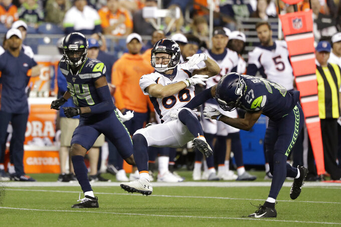 Seattle Seahawks defensive back Marquise Blair, right, hits Denver Broncos wide receiver Nick Williams, center, drawing a penalty flag for unnecessary roughness, as Seahawks defensive back Simeon Thomas, left, watches during the second half of an NFL football preseason game Thursday, Aug. 8, 2019, in Seattle. (AP Photo/Elaine Thompson)