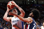 Luis Scola of Argentina puts up a shot over Louis Labeyrie of France during their semifinal match in the FIBA Basketball World Cup at the Cadillac Arena in Beijing, Friday, Sept. 13, 2019. (AP Photo/Mark Schiefelbein)