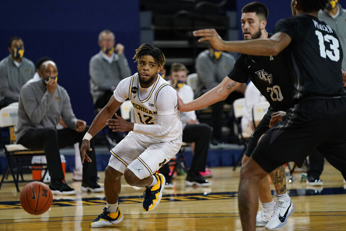 Michigan guard Mike Smith (12) drives around Central Florida forward Sean Mobley (20) during the second half of an NCAA college basketball game, Sunday, Dec. 6, 2020, in Ann Arbor, Mich. (AP Photo/Carlos Osorio)