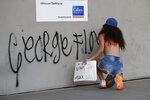 A protester against the death of George Floyd puts graffiti on a wall as she and others demonstrate Sunday, May 31, 2020, in Miami. Floyd died after being restrained by Minneapolis police officers on May 25. (AP Photo/Wilfredo Lee)