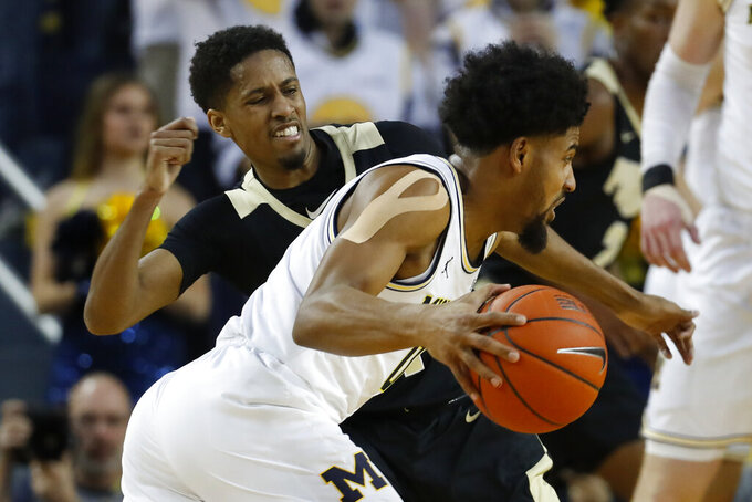 Michigan guard David DeJulius drives on Purdue guard Isaiah Thompson during the first half of an NCAA college basketball game in Ann Arbor, Mich., Thursday, Jan. 9, 2020. (AP Photo/Paul Sancya)