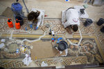 In this Thursday, Dec. 6, 2018 photo, restoration experts work on a mosaic inside the Church of the Nativity, built atop the site where Christians believe Jesus Christ was born, in the West Bank City of Bethlehem. The renovation is lifting spirits in the biblical town of Bethlehem ahead of Christmas, offering visitors a look at ancient mosaics and columns that have been restored to their original glory for the first time in 600 years. (AP Photo/Majdi Mohammed)