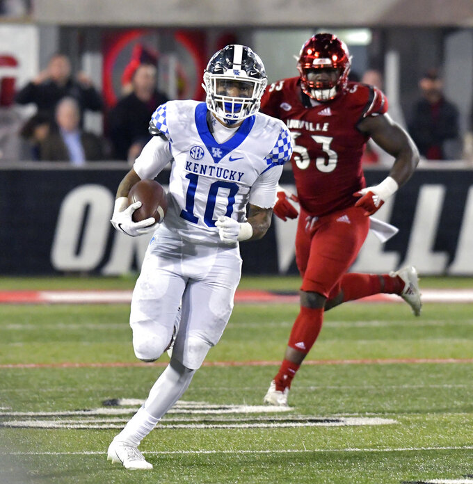 Kentucky running back Asim Rose (10) runs from Louisville defensive end Amonte Caban (53) during the second half of an NCAA college football game in Louisville, Ky., Saturday, Nov. 24, 2018. Kentucky won 56-10. (AP Photo/Timothy D. Easley)