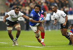 FILE - In this Nov. 24, 2018 file photo, France's Mathieu Bastareaud, centre, runs between Fijian defenders during the rugby international between France and Fiji at Stade de France in Paris. Bastareaud is one of a host of big names to be missing the first Rugby World Cup in Asia. (AP Photo/Christophe Ena,File)