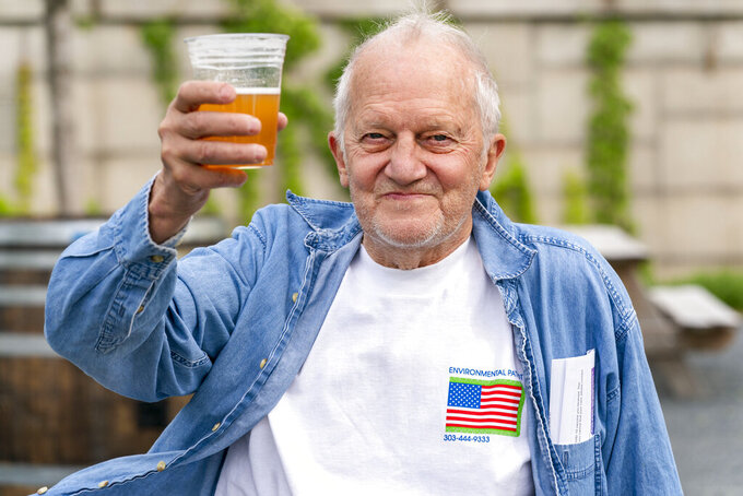"""George Ripley, 72, of Washington, holds up his free beer after receiving the J & J COVID-19 vaccine shot, Thursday, May 6, 2021, at The REACH at the Kennedy Center in Washington. """"I'm relieved to have one and be done with it,"""" says Ripley, """"that's it. I'm happy to be out here."""" People who received a vaccination at the event had the option to have a free beer. (AP Photo/Jacquelyn Martin)"""