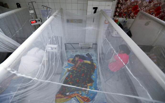 In this photo taken on Aug. 20, 2019, a patient receives treatment for dengue inside a room at the University School Hospital in Tegucigalpa, Honduras. At least 135 people have died from dengue this year in Honduras, nearly two-thirds of them children. (AP Photo/Eduardo Verdugo)