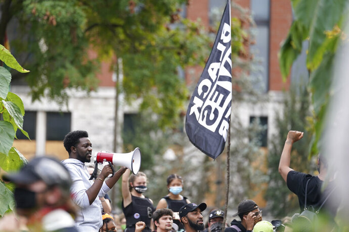 A man speaks to Black Lives Matter protesters, Friday, Sept. 25, 2020, in Louisville. Breonna Taylor's family demanded Friday that Kentucky authorities release all body camera footage, police files and the transcripts of the grand jury hearings that led to no charges against police officers who killed the Black woman during a March drug raid at her apartment. (AP Photo/Darron Cummings)