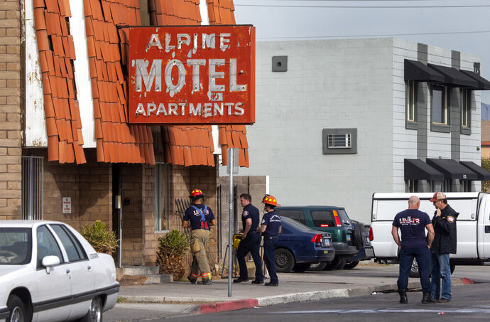 FILE - In this Dec. 21, 2019 file photo Las Vegas firefighters work the scene of a fire at a three-story apartment complex in Las Vegas. The sister of one of six residents found dead after the Las Vegas apartment building fire filed a wrongful death lawsuit Wednesday, Jan. 8, 2020, against the property owner, who officials say had been been cited in the past over missing smoke alarms and an emergency exit that was bolted shut. (Steve Marcus/Las Vegas Sun via AP, File)