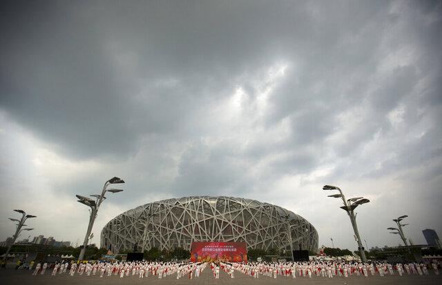 """File-Participants dance under threatening skies at a gathering to watch the announcement of the 2022 Winter Olympics host city outside the Beijing Olympic Stadium, also known as the Birds Nest, in Beijing, Friday, July 31, 2015.  The Olympics are remembered for the stars. That was true in Beijing in 2008, and the stars were Michael Phelps and Usain Bolt. But Beijing is also storied for its signature venues like the """"Bird's Nest"""" stadium, and the """"Water Cube"""" swimming venue. No Olympics before — or since — have impacted a city the way the Olympics did Beijing. (AP Photo/Mark Schiefelbein, File)"""