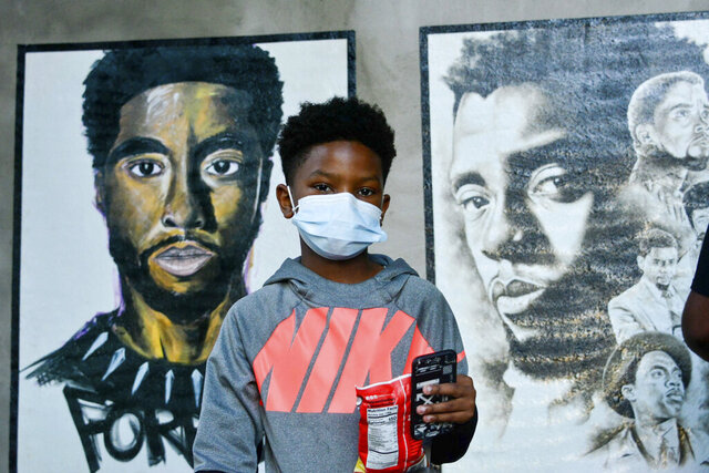 A boy stands in front of two paintings of Chadwick Boseman during the opening of an art exhibit honoring the actor in his hometown of Anderson, S.C. on Thursday, Oct. 22, 2020. Nearly 20 local artists took part in the city sponsored project. (Charles McBryde, Via AP)