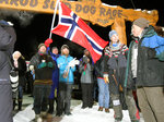 People cheer and wave a Norweigian flag as musher Joar Leifseth Ulsom approaches the finish line to win the Iditarod sled dog race in Nome, Alaska, Wednesday, March 14, 2018. (AP Photo/Diana Haecker)
