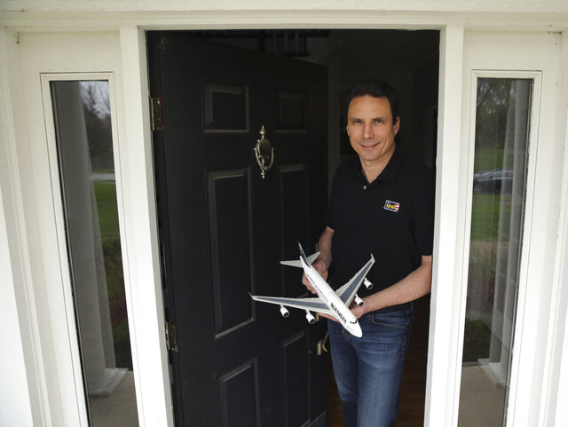 In this April 28, 2020 photo Lou Aguilera, President of Revell North America, holds a model of an Iron Maiden Ed Force One at his home in Cary, Ill. Aguilera says online sales have seen significant growth from people at home looking for something to do. The Illinois-based model kit-maker that emerged from bankruptcy two years ago when purchased by a German investment firm is seeing a resurgence as a result of the coronavirus pandemic. (Stacey Wescott/Chicago Tribune via AP)